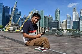 Sharif Uddin berposing dengan bukunya berlatarbelakangkan Singapura ~ foto nstcommy