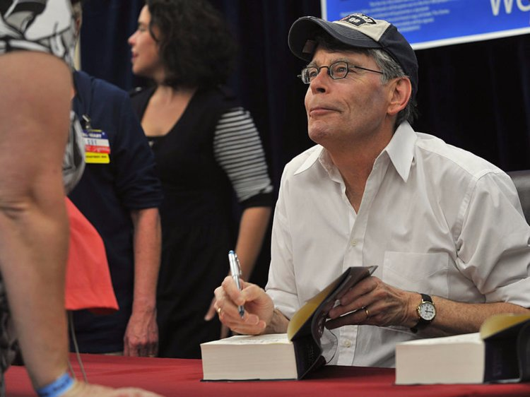 Stephen King menandatangani buku peminat ~ foto businessinsider